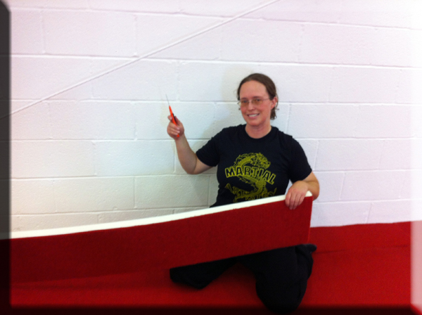 April Dawn Duncan helps put the finishing touches on the flooring during the kung fu school remodel.