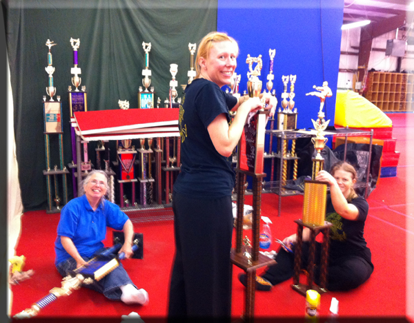 Jen Vossen Dorothy Stender Barbara Wilson cleaning martial arts trophies.